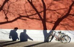 <p>Тени людей на стене здания в Пекине 29 декабря 2008 года. Как и жители большинства развивающихся стран, пекинцы предпочитают передвигаться на автомобилях. Однако велосипед остается зачастую единственным способом быстро доехать до пункта назначения, минуя многокилометровые пробки. Учитывая загазованность города, мэрия Пекина активно поддерживает велосипедное движение. REUTERS/Jason Lee</p>