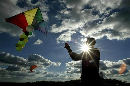 A man is silhouetted as he flys a kite on top of the Teufelsberg hill in Berlin October 15, 2003. REUTERS/Fabrizio Bensch