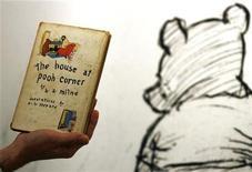 """<p>Сотрудник аукционного дома Sotheby's в Лондоне показывает первое издание книги А.А. Милна про медвежонка Винни-Пуха """"Дом на Пуховой опушке"""", датированное 1928 годом. 15 декабря 2008 года. Некоторые значительные события в мировой истории, произошедшие 18 января. REUTERS/Luke MacGregor (BRITAIN)</p>"""