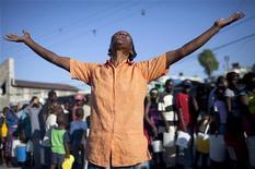 <p>Женщина молится и поет на улице города Порт-о-Пренс 15 января 2010 года. Выжившие в разрушительном землетрясении гаитяне в воскресенье пришли в уцелевшие церкви для молитвы, а те кто опасался новых толчков, молился прямо на улице. REUTERS/Carlos Garcia Rawlins</p>