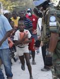 <p>Port-au-Prince, Haiti: un bimbo corre dopo aver ritirato un pacco di aiuti umanitari ai sopravvissuti del terremoto. REUTERS/Tatyana Makeyeva</p>