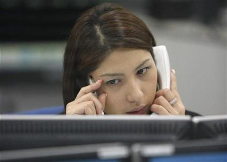A foreign exchange dealer watches a monitor as she talks on the phone at a trading room in Tokyo January 22, 2009. REUTERS/Kim Kyung-Hoon