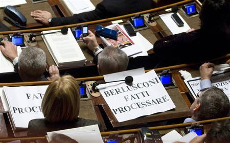 A banner reading ''Berlusconi go to trial'' lies on the desk of an opposition senator during a vote on a bill cutting the duration of the country's trials at the Italy's Senate in Rome January 20, 2010. REUTERS/Remo Casilli