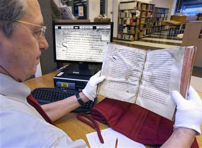 Yves Jocteur Montrozier, chief curator of the old books collection at the Municipal Library of Lyon, displays an old book which has been digitised next to its online copy on a screen in this January 15, 2010 file picture. REUTERS/Robert Pratta