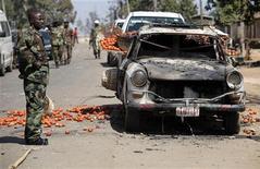 <p>Солдат стоит рядом со сгоревшим автомобилем в городе Джос, Нигерия. 20 января 2010 года. Число жертв столкновений на религиозной почве в нигерийском городе Джос, продолжающихся четвертый день, превысило 460 человек. REUTERS/Akintunde Akinleye</p>