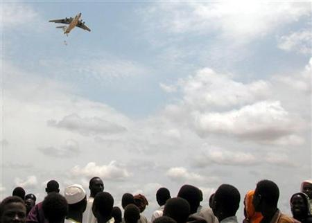 Sudanese displaced people watch a U.N. World Food Programme aircraft drop hundreds of 50-kilogram bags of food aid near the town of Habilla in west Darfur in this file picture released by the WFP on August 14, 2004. REUTERS/WFP/Rathi PalaKrishnan