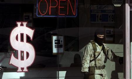 A soldier stands inside a raided pawn shop while under investigation for money laundering in Tijuana November 25, 2009. REUTERS/Jorge Duenes