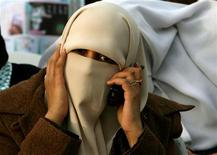 <p>A female Palestinian uses her mobile phone during a campaign rally in Khan Younis refugee camp south of Gaza January 22, 2006. REUTERS/Ahmed Jadallah</p>