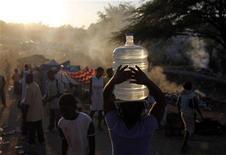 <p>Человек несет канистру с питьевой водой с лагерь беженцев в Порт-о-Пренсе 21 января 2010 года. Правительство Гаити и сотрудники международных гуманитарных организаций делают все возможное, чтобы облегчить участь выживших в страшном землетрясении, произошедшем на острове 12 января и разрушившем столицу Порт-о-Пренс. REUTERS/Eliana Aponte</p>