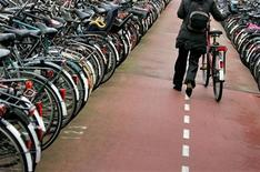 <p>A women walks with her bike in a huge bicycle shed near Central Station Amsterdam, The Netherlands January 17, 2007. REUTERS/Koen van Weel</p>