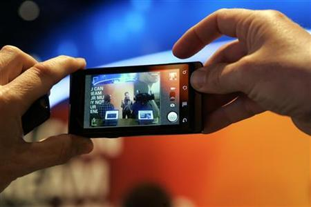 A man takes a photo with a Motorola Milestone smartphone, sister phone to the Motorola Droid, during the 2010 International Consumer Electronics Show (CES) in Las Vegas, Nevada January 8, 2010. REUTERS/Steve Marcus