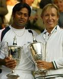 """<p>Американская теннисистка Мартина Навратилова и индийский теннисист Леандер Паес держат кубки после победа на Уимблдонском турнире в смешанном разряде, Лондон 6 июля 2003 года. 26 января 2003 года американская теннисистка Мартина Навратилова стала самой старой спортсменкой, выигравшей турнир """"Большого шлем"""". В возрасте 46 лет она и индийский теннисист Леандер Паес выиграли Уимблдонский турнир в смешанном разряде.REUTERS/Jeff J Mitchell</p>"""