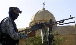 <p>Полицейский в маске стоит рядом с пулеметом около христианского храма в городе Мосул, Ирак. 14 июля 2009 года. Неизвестные в среду утром открыли огонь по двум автобусам с иранскими паломниками в Багдаде, после чего скрылись с места нападения на спортивном автомобиле, сообщила служба безопасности иракской столицы. REUTERS/Khalid al-Mousuly</p>