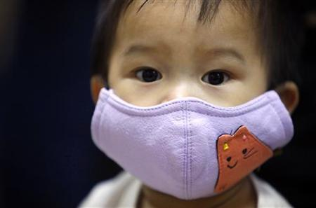 A boy wears a mask before receiving an Influenza A (H1N1) vaccine at a hospital in Taipei November 9, 2009. REUTERS/Nicky Loh