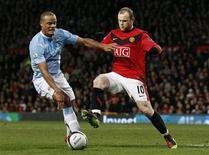 <p>Wayne Rooney do Manchester United (dir.) desafia Vincent Kompany do Manchester City durante o jogo da Copa da Liga Inglesa em Manchester. O Manchester United derrotou por 3 x 1 o Manchester City, vencendo uma sensacional semifinal com resultado global 4 x 3. REUTERS/PhiL Noble 27/01/2010</p>