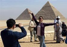 <p>Туристы фотографируются на фоне пирамид, Каир 12 февраля 2009 года. Когда дело доходит до шикарных каникул по приемлемой цене, в первую очередь в голову приходит Египет. Несмотря на круглогодичную жару, путешественников по-прежнему манят великие пирамиды в Гизе. REUTERS/Tarek Mostafa</p>