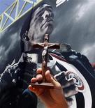 <p>Мужчина молится и держит распятие на фоне постера с изображением парагвайского нападающего Сальвадора Кабаньяса, недалеко от Асунсьона 28 января 2010 года. Парагвайский нападающий Сальвадор Кабаньяс мог сам спровоцировать нападение со стороны неизвестного, выстрелившего ему в голову в одном из баров Мехико, сообщают мексиканские СМИ. REUTERS/Jorge Adorno</p>
