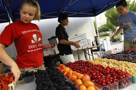 Grace Blackburn, Susan Noyce and Mary Claire Geyer (L-R) set out fruit for sale at the Westmoreland Berry Farm stand at the Arlington Farmers' Market in Arlington, Virginia in this picture taken June 28, 2008. REUTERS/Jonathan Ernst