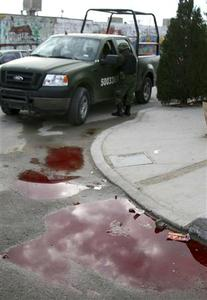 A Mexican soldier stands next to a crime scene in Ciudad Juarez January 31, 2010. REUTERS/Alejandro Bringas