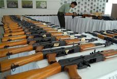 <p>Полицейский снимает на видео конфискованные АК-47 в Кали 12 января 2010 года. Россия поставит Ливии вооружения на 1,3 миллиарда евро ($1,8 миллиарда), сообщили российские агентства со ссылкой на премьер-министра РФ Владимира Путина. REUTERS/Stringer</p>