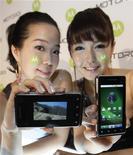 <p>Modelos posan con el nuevo smartphone de Motorola 'Motoroi' en una conferencia de prensa en Seúl, 18 ene 2010. La floreciente demanda de aparatos inteligentes ayudó al mercado global de teléfonos a recuperarse el año pasado, pero la rivalidad por un fragmento de ese lucrativo negocio se volverá feroz en 2010 por la llegada de otros actores al mercado. Strategy Analytics dijo el lunes que el mercado de teléfonos inteligentes creció un 30 por ciento anual en el trimestre que terminó en diciembre hasta los 53 millones de teléfonos, la cifra más alta de la historia. REUTERS/Jo Yong-Hak</p>