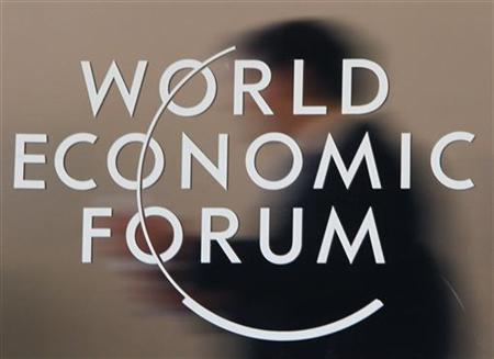 Attendees are reflected behind a logo at the congress centre of the Alpine resort of Davos, the venue of the World Economic Forum (WEF), January 31, 2010. REUTERS/Christian Hartmann (SWITZERLAND - Tags: POLITICS BUSINESS)