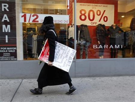 A woman walks past a retail store in the fashion district of New York, January 14, 2010. REUTERS/Brendan McDermid
