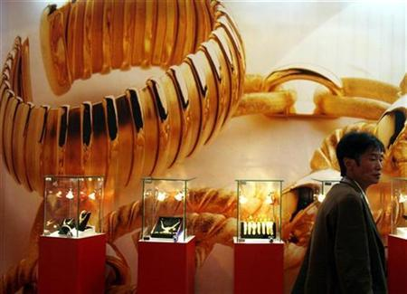 A visitor to the China International Jewellery Fair walks past a poster and gold jewellery display in Beijing November 12, 2008. REUTERS/David Gray