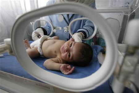 A nurse looks after a premature baby inside an incubator at an Egyptian public hospital in the province of Sharkia to the northeast of Cairo on June 10, 2008. REUTERS/Nasser Nuri