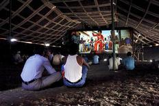 <p>Cinemagoers watch a Bollywood film inside a tent cinema in Pusegaon in this undated handout realised on February 4, 2010. Cut to a far-flung district in western Maharashtra state, where thousands of farmhands attending a religious festival crowd under giant marquees to watch another movie, on another, similar makeshift screen, a few weeks later. REUTERS/Amit Madheshiya/Handout</p>