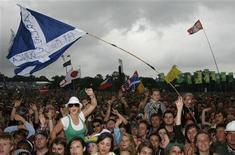 <p>Фанаты танцуют и поют на фестивале Гластонбери, Англия 27 июня 2008 года. Организаторы рок-фестиваля в английском Гластонбери забеспокоились, что некоторые посетители праздника не могут как следует рассмотреть происходящее на сцене из-за многочисленных флагов поклонников. REUTERS/Luke MacGregor</p>