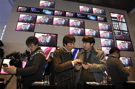 Journalists and visitors look at Samsung Electronics' Android 2.1 platform-based smartphone models during a news conference at the company's headquarters in Seoul February 4, 2010. South Korea's Samsung Electronics said on Thursday it aimed to treble smartphone shipments this year to more than 18 million units as the world's second-biggest cellphone maker scrambles to make a mark in the fast-growing smartphone market. REUTERS/Jo Yong-Hak