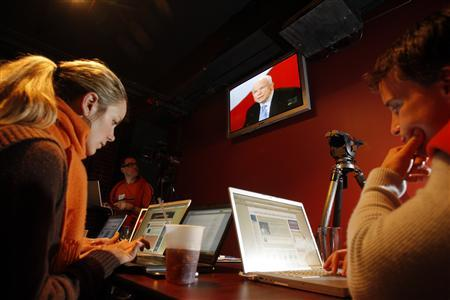 Bloggers Lisa Walker, 32, of Cambridge, Massachusetts (L), and Tom Gerace, 37, of Boston, Massachusetts sit in front of computers while watching the Republican Debate from a bar in Manchester, New Hampshire in this January 5, 2008 file photo. REUTERS/Jessica Rinaldi