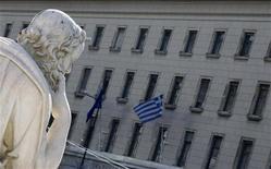 <p>Флаг Греции на здании Банка Греции виден недалеко от статуи Сократа в Афинах 5 февраля 2010 года. Греция попыталась в пятницу побороть скептицизм инвесторов относительно планов значительно сократить дефицит государственного бюджета в ближайшие годы и пообещала добиться четкой реализации налоговых реформ и ряда других решений для достижения этой цели. REUTERS/Yiorgos Karahalis</p>