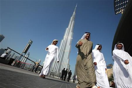 A group of Emiratis walk past the Burj Dubai Tower, the tallest tower in the world, on the day of its inauguration, in Dubai January 4, 2010. REUTERS/Ahmed Jadallah