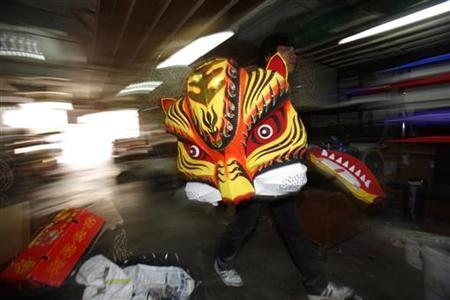 A worker carries a replica of a tiger head which they use for the Chinese Tiger Dance, ahead of the Lunar New Year celebrations at a shop in Shah Alam outside Kuala Lumpur February 9, 2010. REUTERS/Bazuki Muhammad