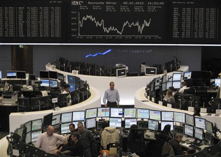 Traders are pictured at their desks in front of the DAX board at the Frankfurt stock exchange February 8, 2010. REUTERS/Remote/Michael Leckel