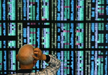 A man looks at stock market prices on computer monitors inside a securities company in Taipei October 28, 2008. REUTERS/Nicky Loh (TAIWAN)