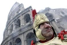 <p>Мужчина, переодетый в костюм древнеримского воина, стоит перед Колизеем во время снегопада, Рим 12 февраля 2010 года. Туристы фотографировали заваленный снегом Колизей в эту пятницу, когда Рим накрыл сильнейший снегопад за последнюю четверть столетия. REUTERS/Alessandro Bianchi</p>