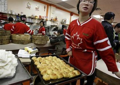 A waitress, wearing a Team Canada ice hockey jersey, passes a tray of freshly baked buns in Chinatown's New Town bakery during the Vancouver 2010 Winter Olympics February 14, 2010. REUTERS/Chris Helgren