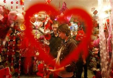 Tourists buying Valentine gifts are seen through a window of a gift shop in Cairo February 13, 2010. REUTERS/Asmaa Waguih