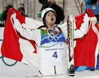 <p>Canada's Alexandre Bilodeau yells out while holding the Canadian flag after winning the gold medal during the men's freestyle skiing moguls on Cypress Mountain at the Vancouver 2010 Winter Olympics February 14, 2010. REUTERS/Mike Blake</p>