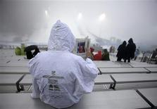 <p>A fan reads a newspaper in the rain and fog at the finish area of the women's snowboard cross event during a weather delay at the Vancouver Winter Olympics Games on Cypress Mountain February 16, 2010. REUTERS/Mark Blinch</p>