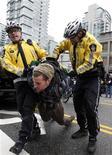 <p>Полиция уводит участника акции протеста против зимних Олимпийских игр 2010 года в центре Ванкувера 13 февраля 2010 года. Канадская полиция арестовала мужчину, подозреваемого в организации антиолимпийских протестов в Ванкувере. REUTERS/Chris Helgren</p>