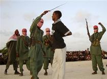 <p>Член Джамаат Аш-Шабааб бьет плетью одного из четырех малодых людей, обвиненных в изнасиловании, на окраине Могадишо 9 марта 2009 года. Суд Саудовской Аравии приговорил сотрудника религиозной полиции королевства к 120-ти ударам плетью за то, что он женился сразу на шести женщинах. REUTERS/Feisal Omar</p>