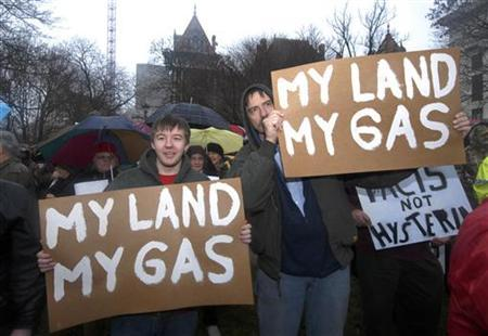 Alex Knapp (L) and his father Albert Knapp of Berkshire, hold placards as they protest in favor of the drilling process of hydraulic fracturing to extract natural gas at the Capitol in Albany, New York January 25, 2010. REUTERS/Hans Pennink