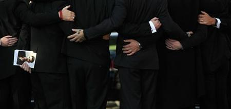The remaining members of Boyzone and members of Stephen Gately's family comfort each after attending his funeral at St Laurence O'Toole church in Dublin, Ireland, October 17, 2009. REUTERS/Cathal McNaughton