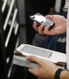 <p>Dans le métro new-yorkais, un Kindle dans une main, un Blackberry dans l'autre. Amazon a lancé une application gratuite Kindle à destination de divers modèles de la gamme Blackberry, qui auront ainsi accès à plus de 420.000 livres. /Photo prise le 1er juin 2009/REUTERS/Lucas Jackson</p>