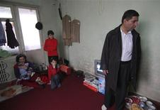 <p>Abdul Mutalib (R), an Afghan refugee in Tajikistan, stands next to his family in an apartment in the Tajik town of Vakhdat, some 200 km (125 miles) north of the Afghan border, January 20, 2010. REUTERS/Nozim Kalandarov</p>