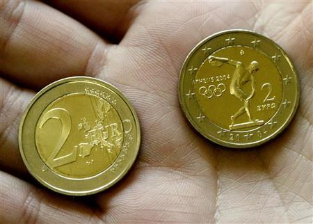 A woman shows in her hand the two sides of a two Euro commemorative coin launched in Athens May 12, 2004, to celebrate the return of the 2004 Olympics to their birthplace.